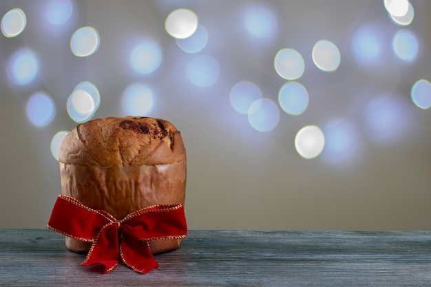 Panettone di torta al cioccolato natalizia con un nastro rosso in uno sfondo chiaro o panettone chocotone