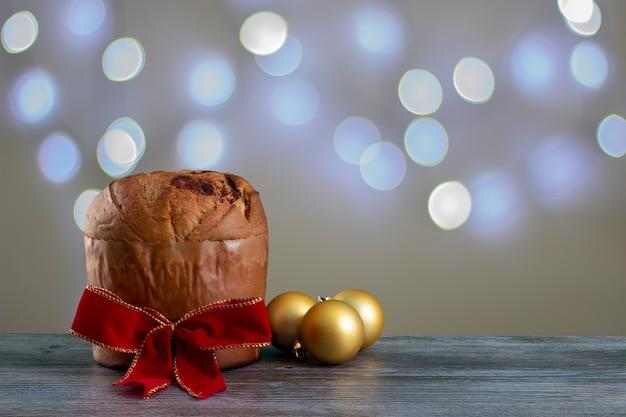 Panettone di torta al cioccolato di natale con un nastro rosso in uno sfondo chiaro, panetone cho