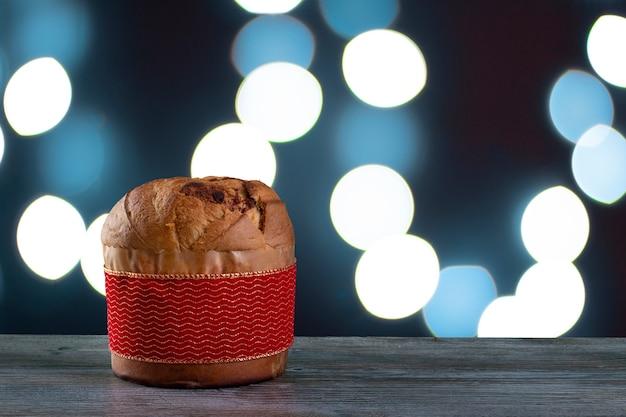 Panettone di torta al cioccolato di natale con una striscia rossa in uno sfondo a luce blu o chetotone panetone
