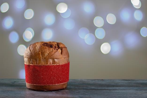 Panettone di torta al cioccolato di natale con una striscia rossa in uno sfondo chiaro o panettone chocotone