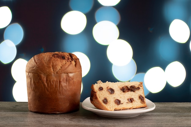 Panettone di torta al cioccolato di natale con una fetta in uno sfondo di croma o chetotone di panetone