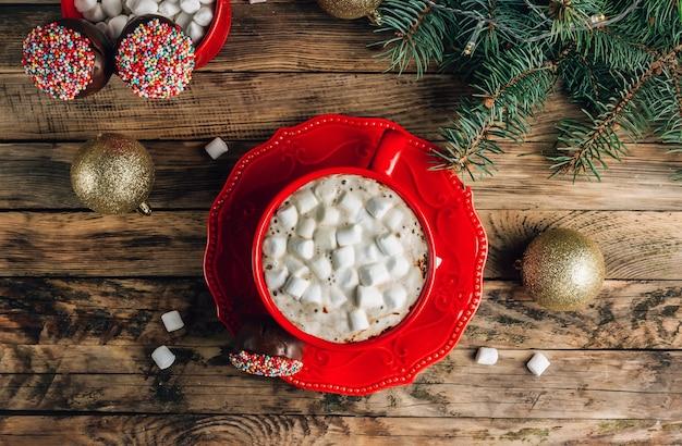 La torta al cioccolato di natale si apre sul cestino rosso con la tazza di caffè con marshmallow su un fondo di legno rustico vista dall'alto