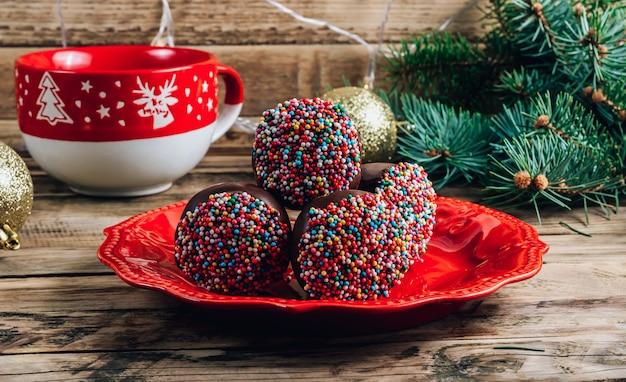 Torta al cioccolato di natale si apre sul piatto rosso con una tazza di caffè con marshmallow su uno sfondo di legno rustico messa a fuoco selettiva