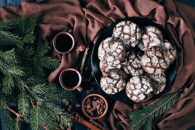 Christmas chocolate crinkle cookies su una piastra nera su un tavolo in legno nero con abete, bastoncini di zucchero, panno marrone e tazze di caffè, scuro in stile rustico, vista dall'alto, flatlay