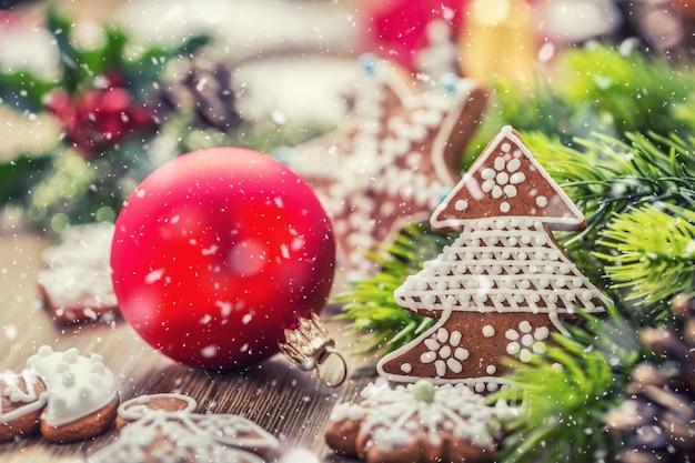 Natale. cono e decorazione del pino del pan di zenzero della pasticceria della palla di natale nell'atmosfera nevosa.
