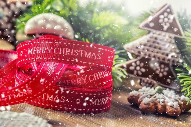 Natale. pan di zenzero e decorazione della pasticceria del nastro di natale nell'atmosfera nevosa.