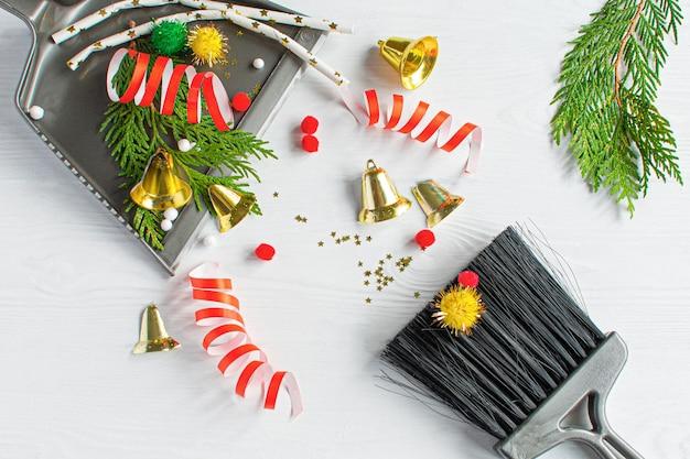 Pulizie di natale dopo. strumenti di pulizia scopa e paletta e decorazioni natalizie inutilizzate dopo la vista dall'alto della festa laici piatta. concetto di pulizia dopo le vacanze, ripulire il disordine.