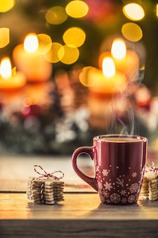 Caffè di natale e corona dell'avvento sul tavolo con luci boheh sullo sfondo.