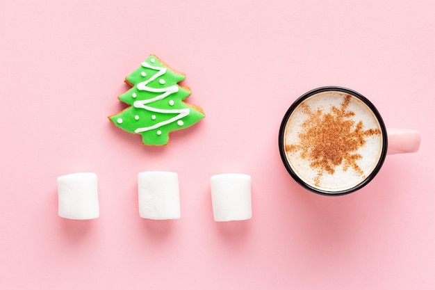 Caffè di natale con biscotto e marshmallow su sfondo rosa, layout piatto. pan di zenzero a forma di albero di abete e latte decorato con fiocco di neve.