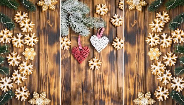 Collage di natale. pan di zenzero e cuori decorativi sui precedenti di legno