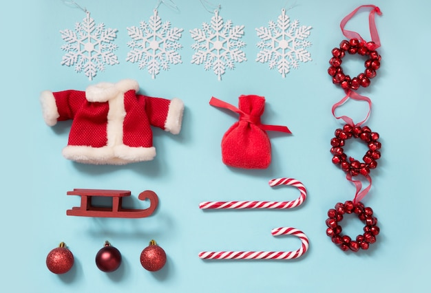 Collezione natalizia con giacca di babbo natale, bastoncini di zucchero, fiocchi di neve sul blu.
