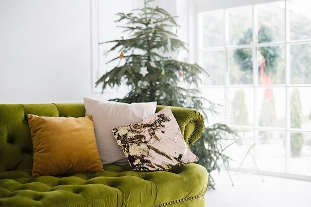 Comfort natalizio. albero di natale, cuscini sul divano verde nel luminoso soggiorno