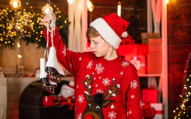 Natale in arrivo. concetto di umore natalizio. bambino di babbo natale. buone vacanze invernali. piccolo ragazzo. bambino del ragazzino in cappello rosso della santa. trasforma le tue scarpe in pattini da ghiaccio per l'inverno. festa di fine anno.