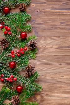 Compisition di natale con albero di natale e bacche rosse sulla tavola di legno