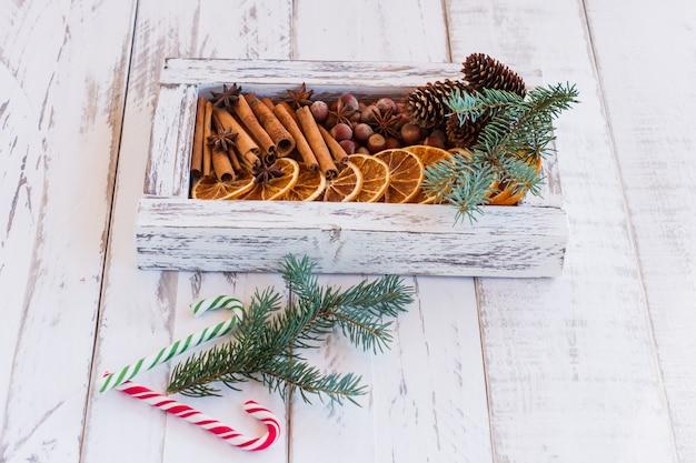 Composizione di natale. disposizione di arance secche, bastoncini di cannella, stelle di anice e noci in una scatola. rami di albero di pelliccia e bastoncini di zucchero su fondo di legno. ingredienti rustici, spezie per le feste.