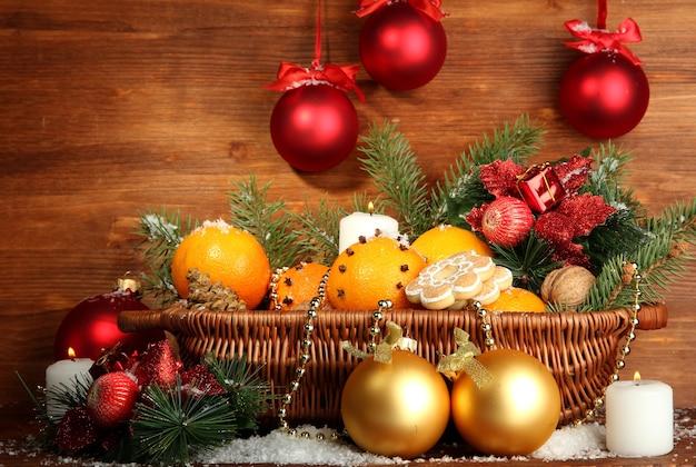 Composizione natalizia in cesto con arance e abete, su fondo in legno