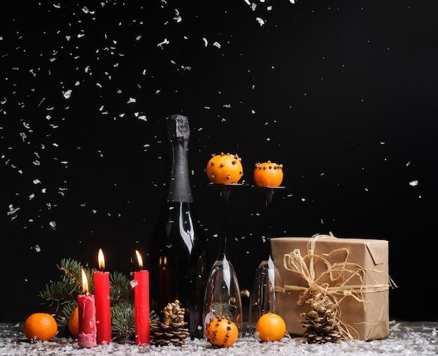 Composizione in natale su sfondo nero con confezione regalo, mandarini, candele pigne rosse, bottiglia di champagne e due bicchieri empy.