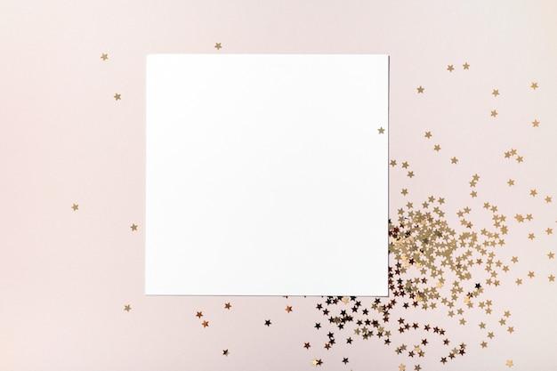 Composizione di natale. mockup di carta quadrata vuota, gioielli di coriandoli di stelle dorate su sfondo beige