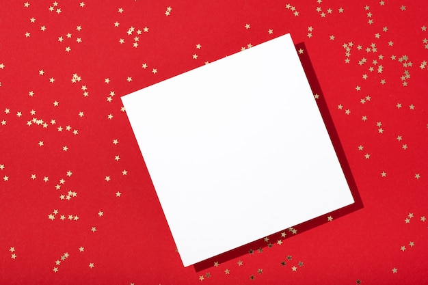 Composizione di natale. mockup di carta quadrata vuota, gioielli di coriandoli di stelle dorate su sfondo rosso