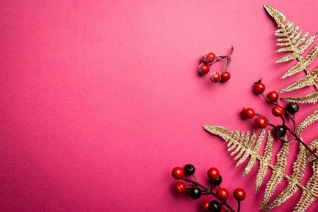 Composizione natalizia rami di bacche rosse su sfondo rosa natale inverno capodanno concept