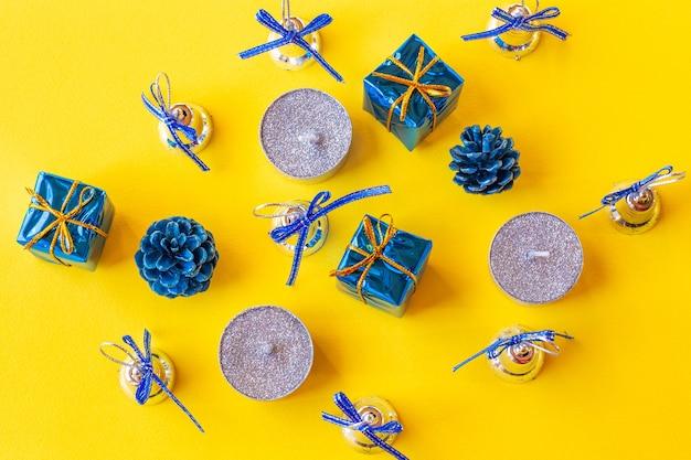 Composizione di natale. candele e decorazioni natalizie in blu su sfondo giallo. appartamento laico, vista dall'alto, copia dello spazio