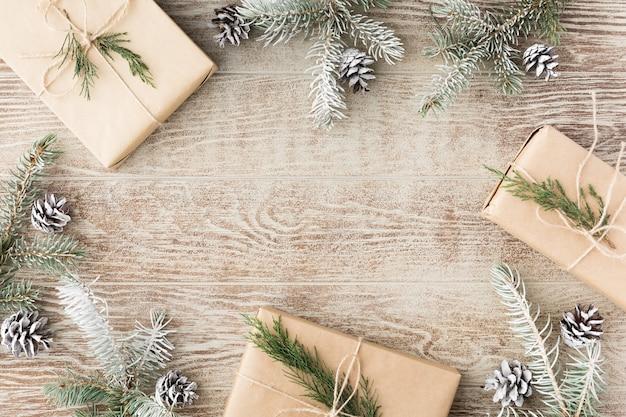 Composizione di natale. rami di abete di natale, regali, pigne su fondo rustico bianco di legno. disposizione piana, vista dall'alto. copia spazio. sfondo banner