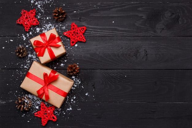 Composizione natalizia. regali di natale con le stelle decorative rosse da rattan e coni su priorità bassa nera di legno. concetto di biglietto di auguri. vista dall'alto, disteso, copia spazio.