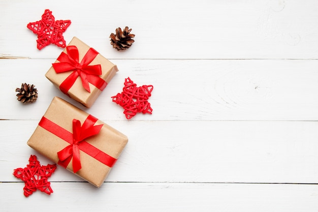 Composizione natalizia. regali di natale con le stelle decorative rosse da rattan e coni su priorità bassa bianca di legno. concetto di biglietto di auguri. vista dall'alto, disteso, copia spazio.