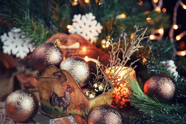 Composizione di natale. decorazione di natale e capodanno con rami di abete, candele e luci natalizie su fondo in legno