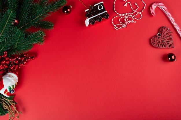 Composizione di natale. decorazioni di natale rosso, rami di albero di natale su sfondo rosso. appartamento laico, vista dall'alto, copia dello spazio.