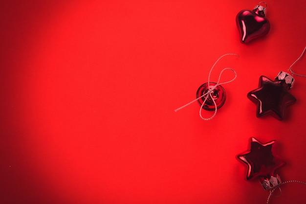 Composizione di natale. decorazioni rosse di natale, fondo rosso delle pigne. disposizione piana, vista dall'alto, copia spazio