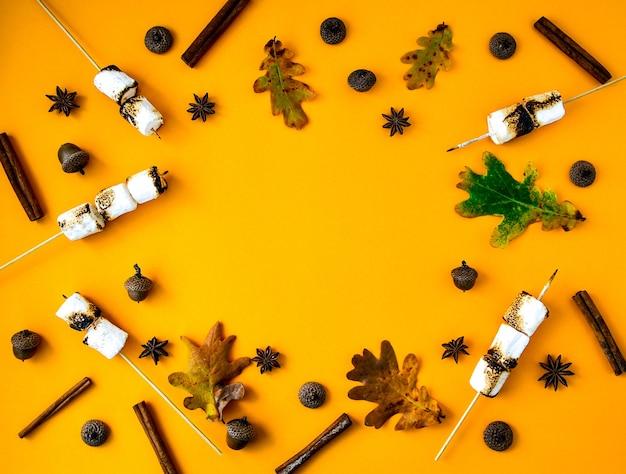 Composizione di natale. foglie di marshmallow alla cannella e anice su sfondo giallo. composizione autunnale. modello fatto di cose autunnali. disposizione piatta. ornamento per il ringraziamento. cornice autunnale con spazio di copia.