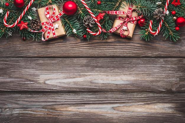 Composizione di natale. rami di abete, scatole regalo, decorazioni, caramelle, pigna sulla tavola di legno