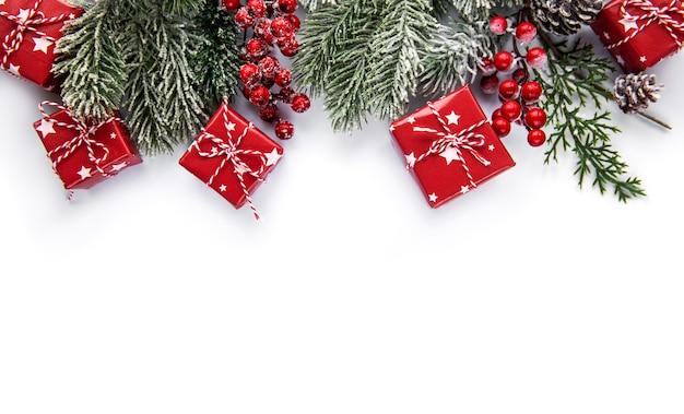 Composizione di natale. rami di abete, decorazioni rosse su bianco