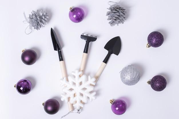 Composizione natalizia di attrezzi da giardino rastrello, pale e palline viola e argento di capodanno, coni, fiocchi di neve su sfondo bianco. può essere usato come biglietto di natale e capodanno per i giardinieri