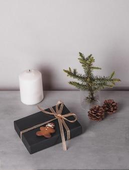 Composizione natalizia regalo decorazioni nere e dorate su sfondo di pietra grigia biscotti