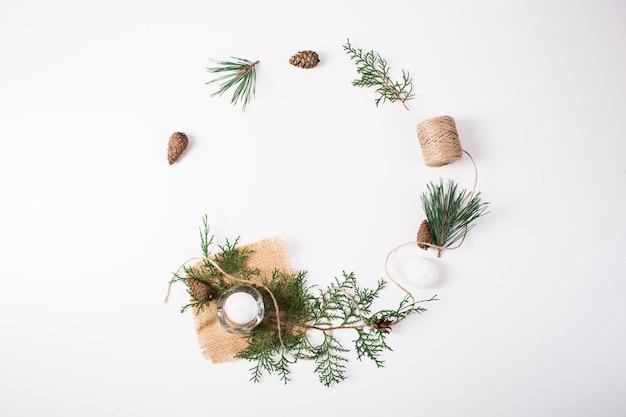 Composizione di natale. regalo, decorazioni natalizie, rami di cipresso, pigne su sfondo bianco