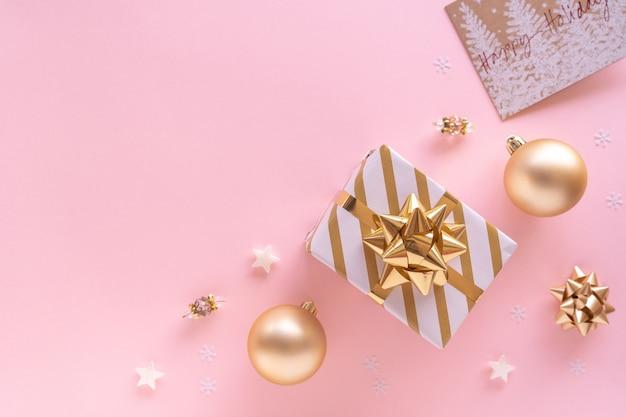 Composizione di natale. confezione regalo, palline, biglietto di auguri, decorazioni dorate su superficie rosa pastello. natale, inverno, concetto di capodanno. appartamento laico, vista dall'alto, copia dello spazio dall'alto.