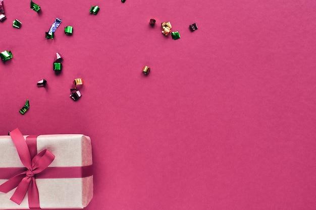 Composizione di natale. confezione regalo con nastro rosso e decorazioni di coriandoli su sfondo colorato di carta pastello. natale, inverno, concetto di celebrazione del nuovo anno. disposizione piana, vista dall'alto, copia spazio