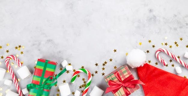 Composizione di natale. regali, canna di caramello, marshmallow, cappello da babbo natale su sfondo grigio cemento con stelle scintillanti.