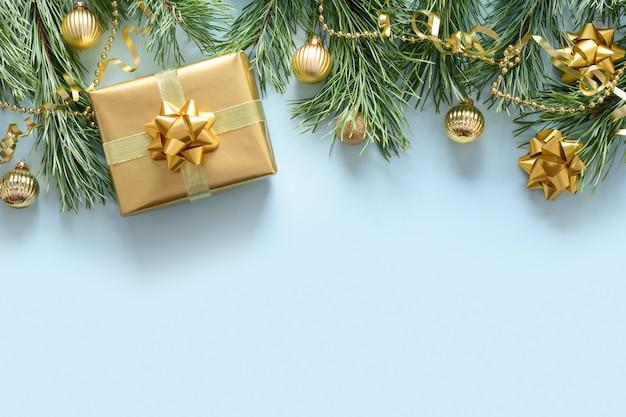 Composizione in natale di rami e palline sempreverdi regalo dorato su sfondo blu