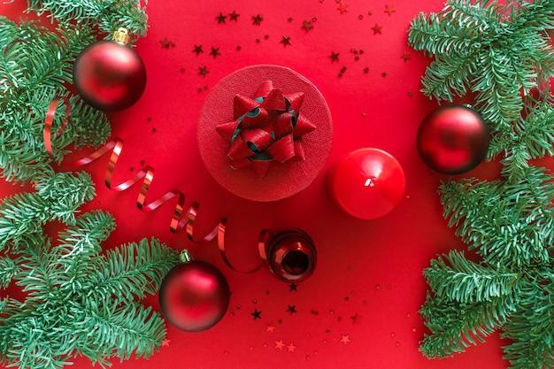 Composizione in natale fatta di regalo di natale, candele, rami di pino, palline sulla superficie rossa. buon natale e felice anno nuovo concetto