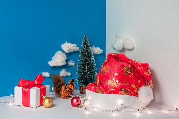Composizione natalizia fatta di cappello da babbo natale e decorazioni natalizie in uno spazio tridimensionale con confezione regalo di luci natalizie con nastro rosso e palline di scoiattolo vista frontale