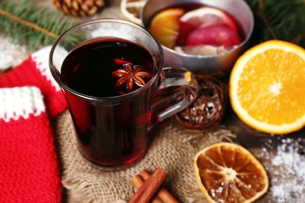 Composizione natalizia di vin brulé, cannella, pino e guanti a maglia rossi su fondo di legno
