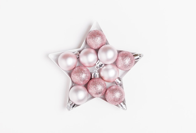 Composizione di natale. palle di natale rosa e argento disposte a forma di stella su sfondo bianco.