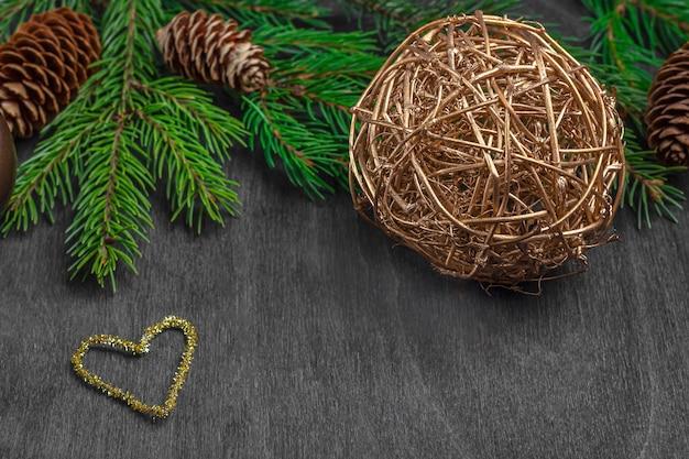 Composizione di natale per cartolina, copertina, banner. rami e palle dell'abete, cono su legno rustico. concetto di nuovo anno. primo piano, copia spazio per il testo.