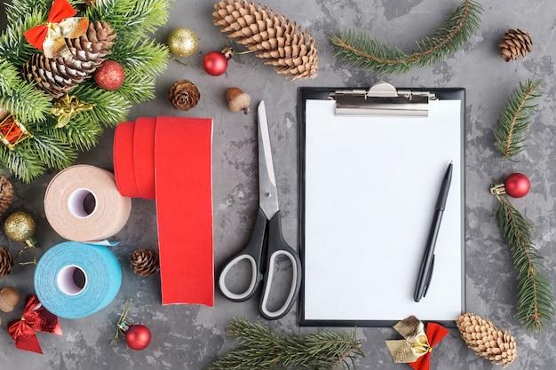 Composizione natalizia di rotoli di nastro kinesiologico per atleti, ghirlande, abeti, pigne, palline, nastri e appunti