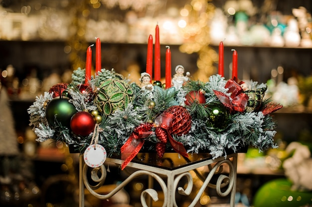 Composizione in natale di rami di abete innevati, candele, nastri, palline giocattolo rosse e verdi
