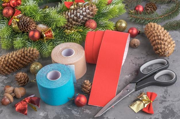 Composizione natalizia di stack rotoli nastro kinesiologico per atleti, ghirlande, abeti, pigne, palline, nastri e forbici