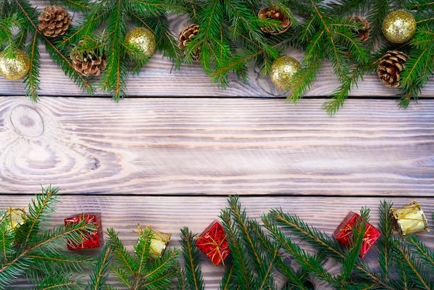 Giocattoli di composizione in natale, regali e rami di un telaio di albero di natale su fondo di legno.